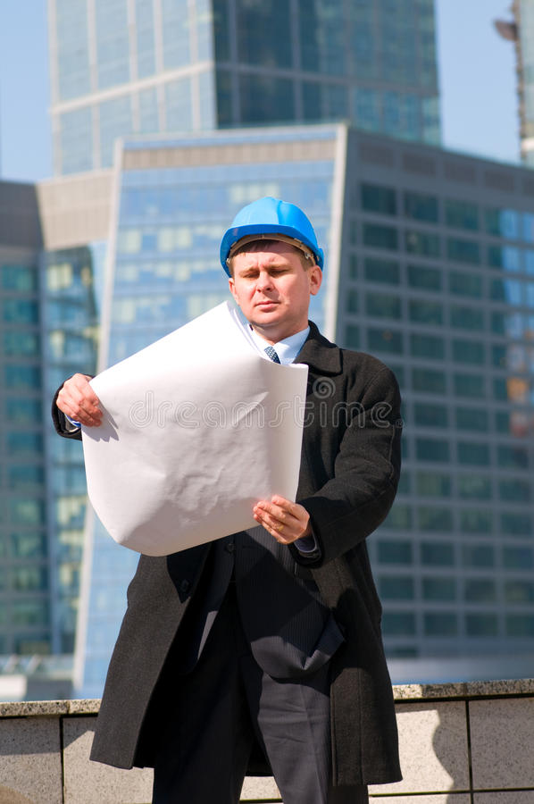 Engineer with blue hard hat holding drawing stock image