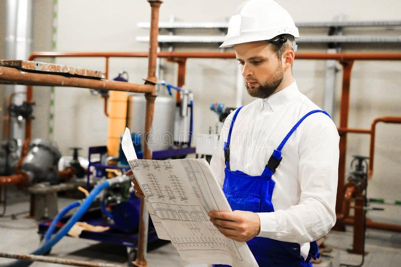 Engineer with blueprints on industrial plant. Manager in industry. Service maintenance on oil factory stock photography