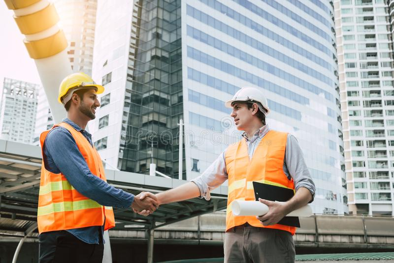 Engineer Boss get handshake, saying thank you to blue collar worker or team for doing work successfully. Employee happy. Blue royalty free stock photography