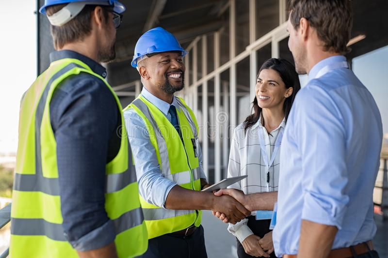 Engineer and businessman handshake at construction site royalty free stock photos