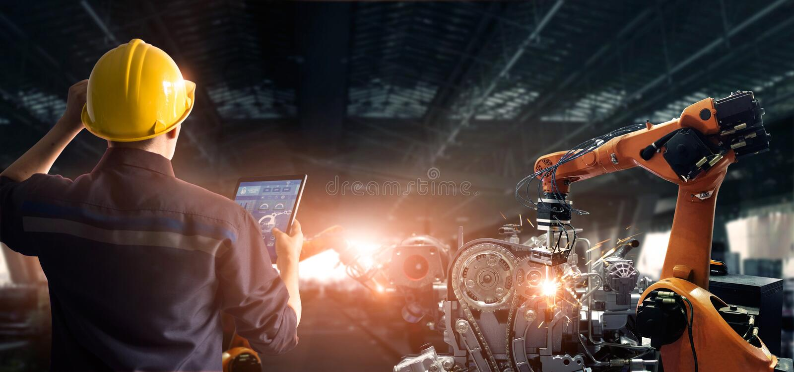 Engineer check and control welding robotics automatic arms machine in intelligent factory automotive industrial with monitoring sy. Stem software. Digital royalty free stock photo