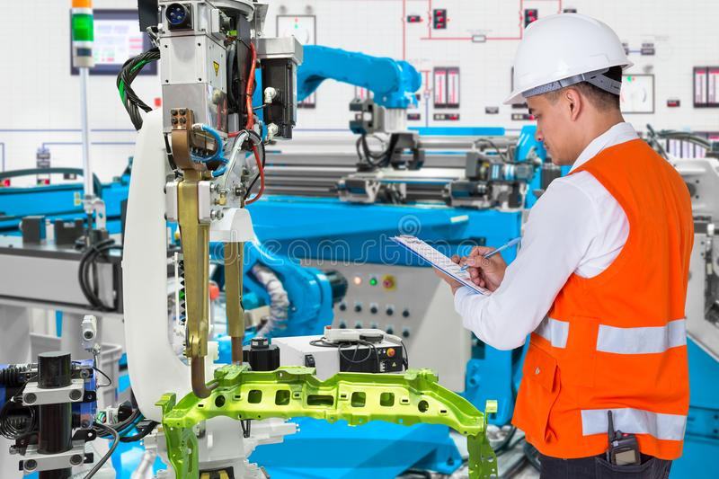 Engineer check maintenance daily of automated automotive robot. Engineer checking maintenance daily of automated automotive robotic in production line of stock image