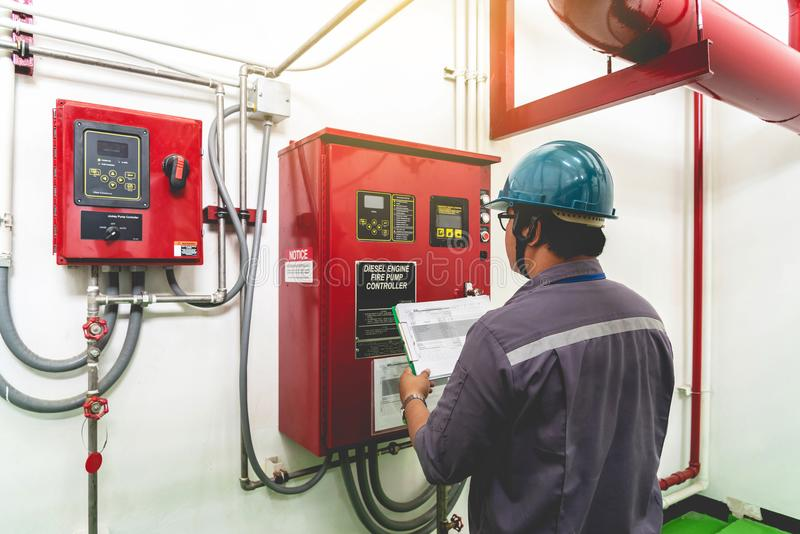 Engineer checking industrial generator fire control system. Diesel engine fire pump controller stock photography