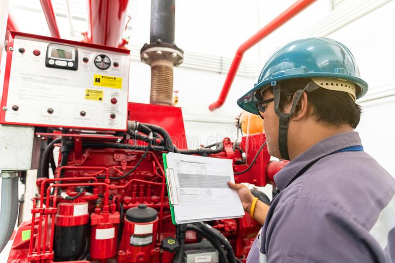 Engineer checking industrial generator fire control system. Diesel engine fire pump controller stock image