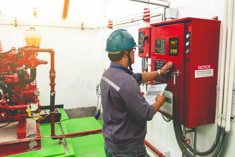 Engineer checking industrial generator fire control system. Diesel engine fire pump controller stock photo