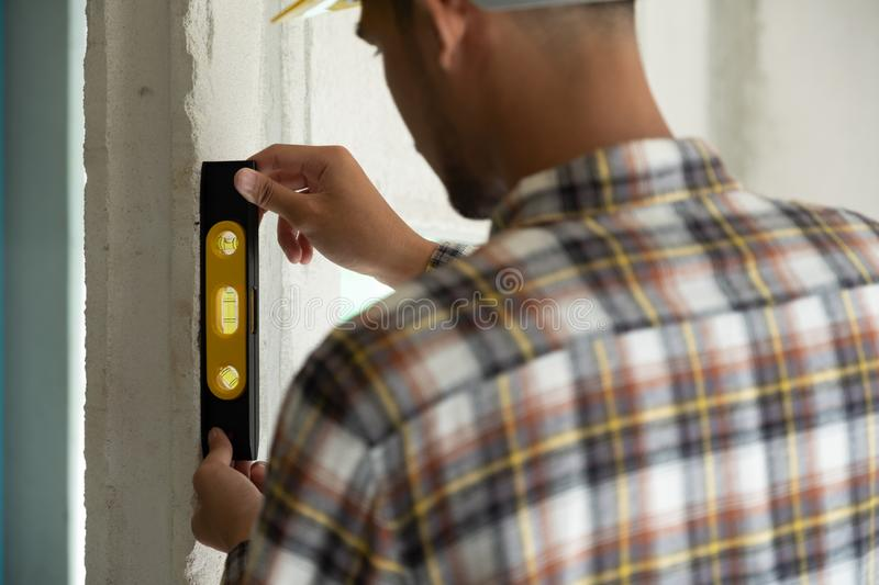 Engineer is checking wall level in building site royalty free stock images