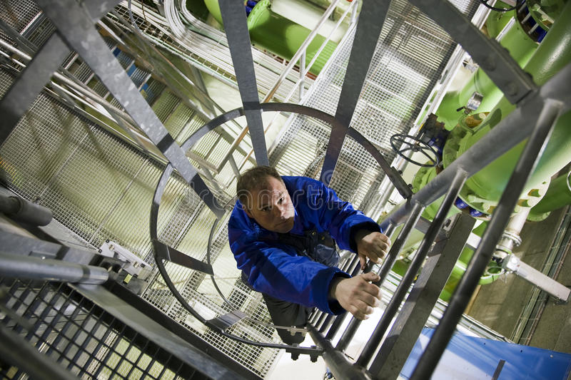 Engineer climbing in plant stock photo
