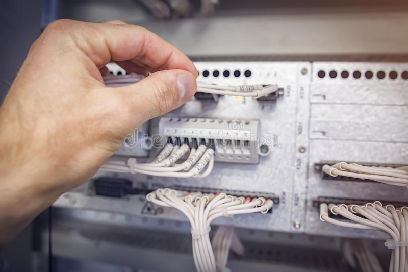 Engineer connects wires to the connector of industrial control controller in electrical cabinet closeup. royalty free stock images