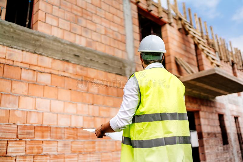 engineer on construction site background, man wearing safety vest, hard top on construction site stock image