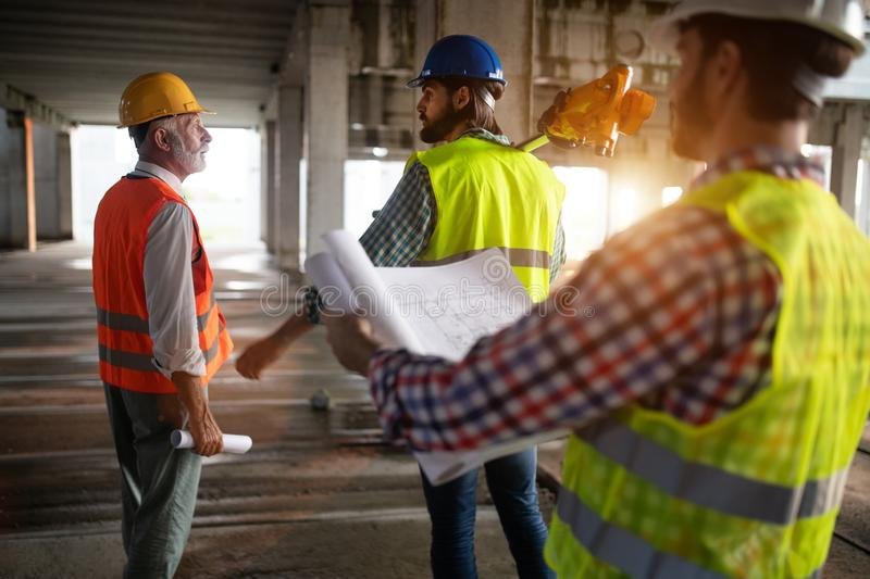 Engineer and construction site manager dealing with blueprints and plans. Engineer and construction site manager working with blueprints and plans royalty free stock image