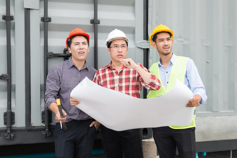 Engineer and construction team wearing safety helmet and blueprint on hand. they are reviewing material and construction process royalty free stock photo