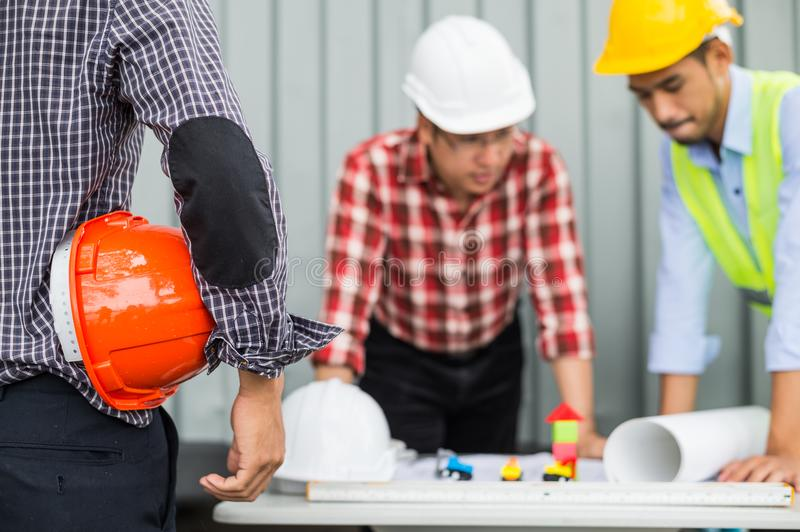 Engineer and construction team wearing safety helmet and working by checking progress of construction in blueprint. royalty free stock photo