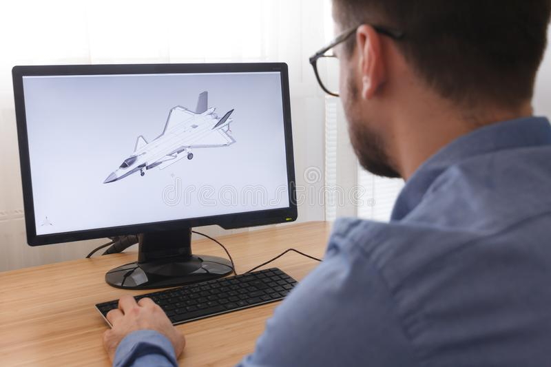 Engineer, Constructor, Designer in Glasses Working on a Personal Computer. He is Creating, Designing a New 3D Model of Aircraft, royalty free stock photo