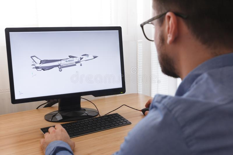 Engineer, Constructor, Designer in Glasses Working on a Personal Computer. He is Creating, Designing a New 3D Model of Aircraft,. Airplane in CAD Program royalty free stock image