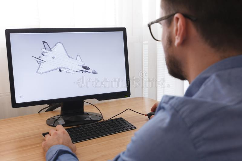 Engineer, Constructor, Designer in Glasses Working on a Personal Computer. He is Creating, Designing a New 3D Model of Aircraft, royalty free stock photography