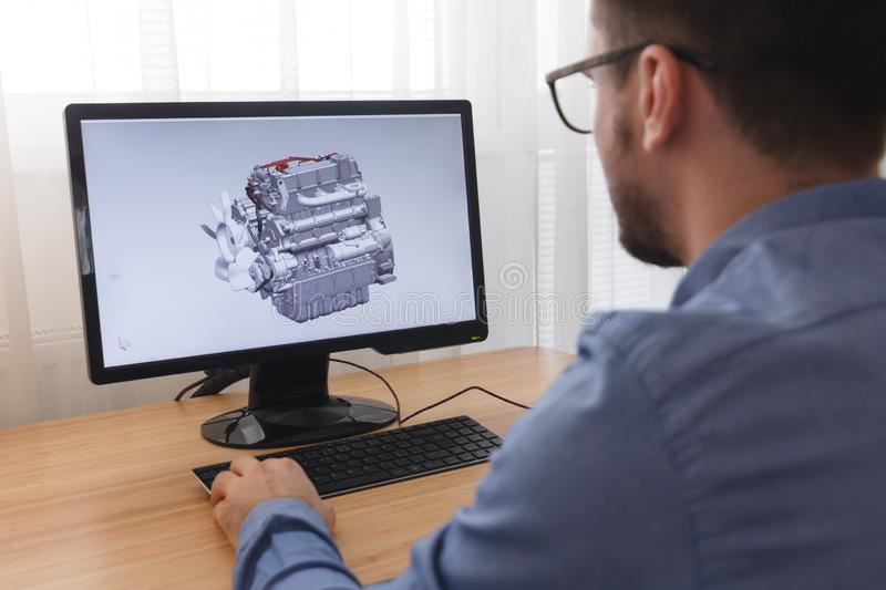 Engineer, Constructor, Designer in Glasses Working on a Personal Computer. He is Creating, Designing a New 3D Model of Car Engine royalty free stock images