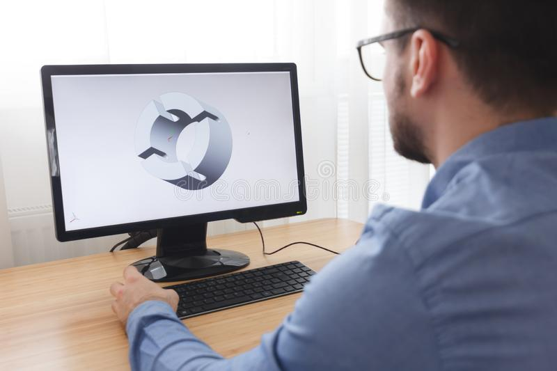 Engineer, Constructor, Designer in Glasses Working on a Personal Computer. He is Creating, Designing a New 3D Model of Mechanical stock photography