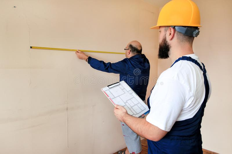 Engineer, contractor and project manager with his colleague, construction worker, handyman and builder is measuring wall of room. stock photo