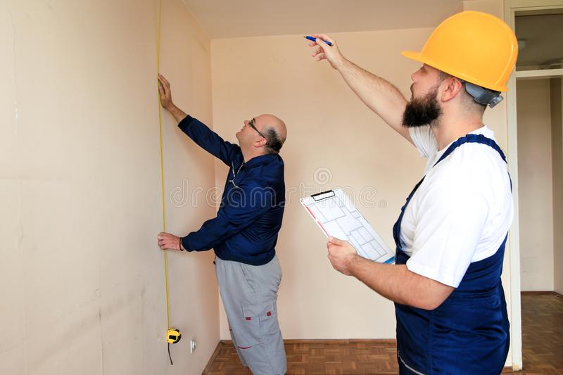Engineer, contractor and project manager with his colleague, construction worker, handyman and builder is measuring wall of room. royalty free stock photography