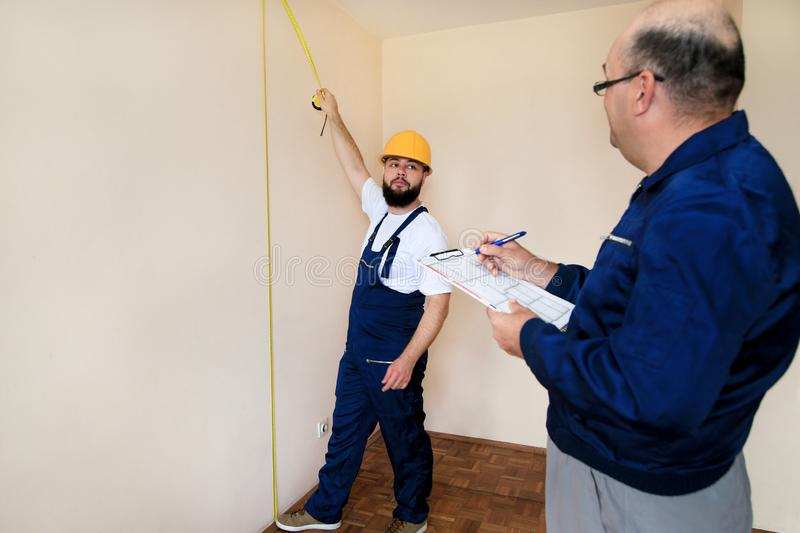 Engineer, contractor and project manager with his colleague, construction worker, handyman and builder is measuring wall of room. royalty free stock images