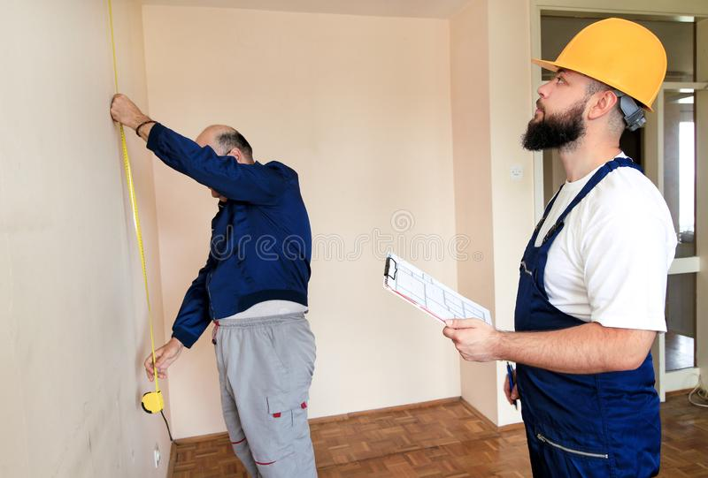 Engineer, contractor and project manager with his colleague, construction worker, handyman and builder is measuring wall of room. royalty free stock photo