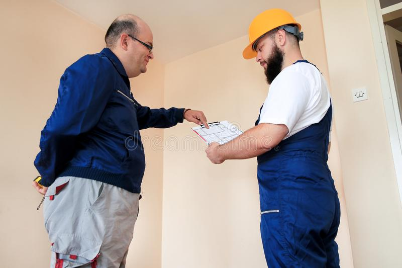 Engineer, contractor and project manager with their colleague construction worker with construction apartment blueprint. stock photo
