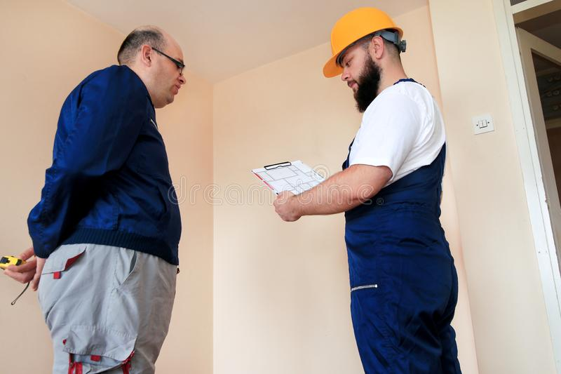 Engineer, contractor and project manager with their colleague construction worker with construction apartment blueprint. royalty free stock images