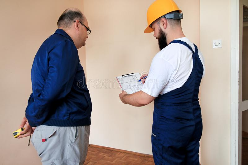 Engineer, contractor and project manager with their colleague construction worker with construction apartment blueprint. royalty free stock photography