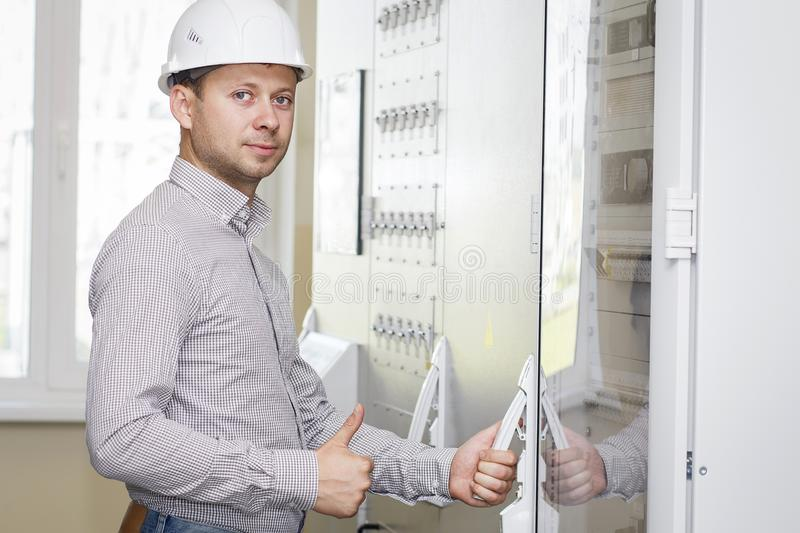 Engineer in control panel room. Worker in white helmet on industrial tech station. Engineer on a job. royalty free stock image