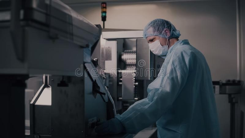 Engineer control pharmaceutical manufacturing. Factory worker operating pharmaceutical equipment. Pharmacy industry royalty free stock image