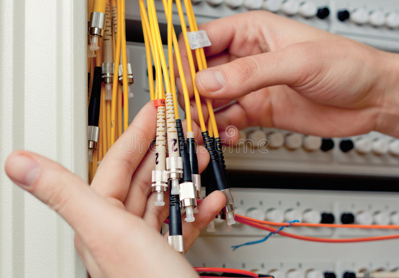 The engineer in a data processing center. The engineer in a data processing center of ISP Internet Service Provider hold fiber patch cords stock images