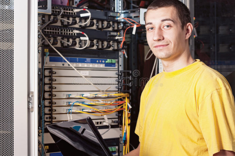 The engineer in datacenter. The engineer stand in datacenter near telecomunication equipment and smiling