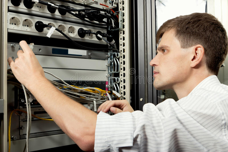 The engineer in datacenter. The engineer stand in datacenter near telecomunication equipmant and looking at ethernet path cord