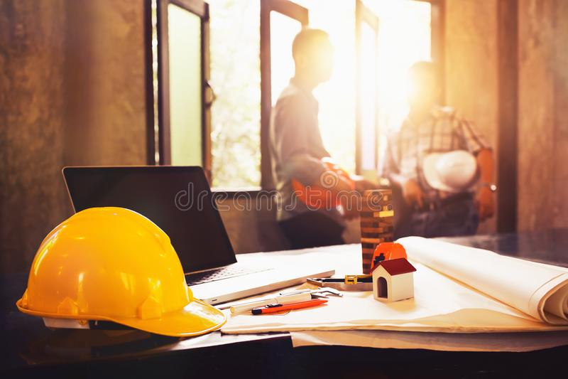 Engineer desk with object and paper with blurry engineer teamwork hardworking to consults about their small business building pro. Ject royalty free stock photography