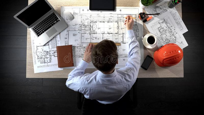 Engineer drawing plan of building, safety engineering, office location planning royalty free stock images