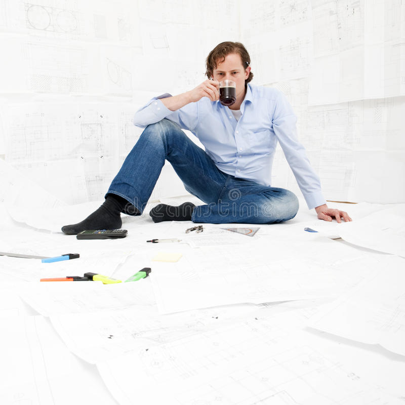 Engineer drinking coffee. An engineer taking a break from reviewing technical drawings, drinking coffee stock image