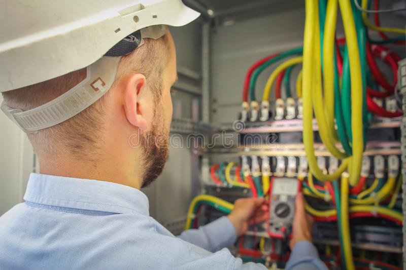 Engineer electric measures multimeter voltage of high-power electrical circuits. royalty free stock photography