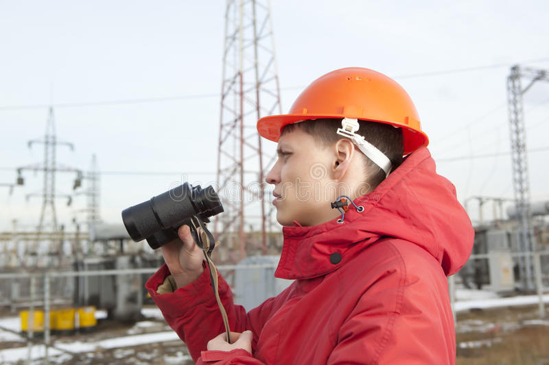 Engineer at Electrical Substation looks through a binoculars stock image