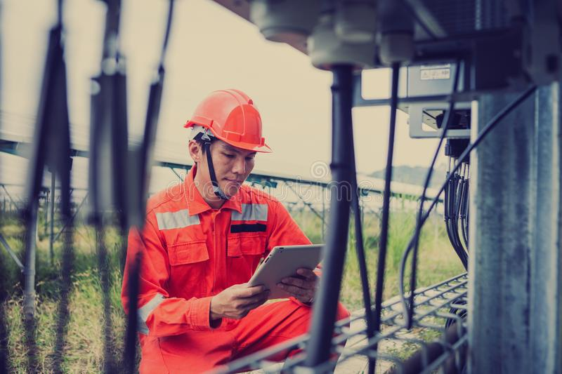 Engineer or electrician holding laptop for inspect and checking string inverter by wifi technology ;smart technology for operate royalty free stock photography