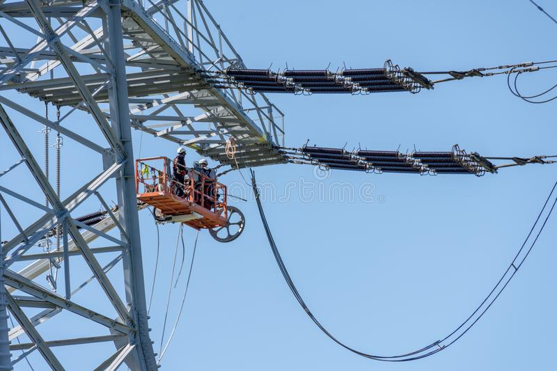 Engineer Electrician Workers On Lift Repairing Electricity Pylon Powerline stock photo