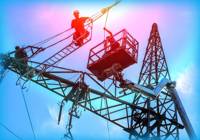 Engineer Electrician Workers On Lift Repairing Electricity Pylon Powerline And Wires royalty free stock images
