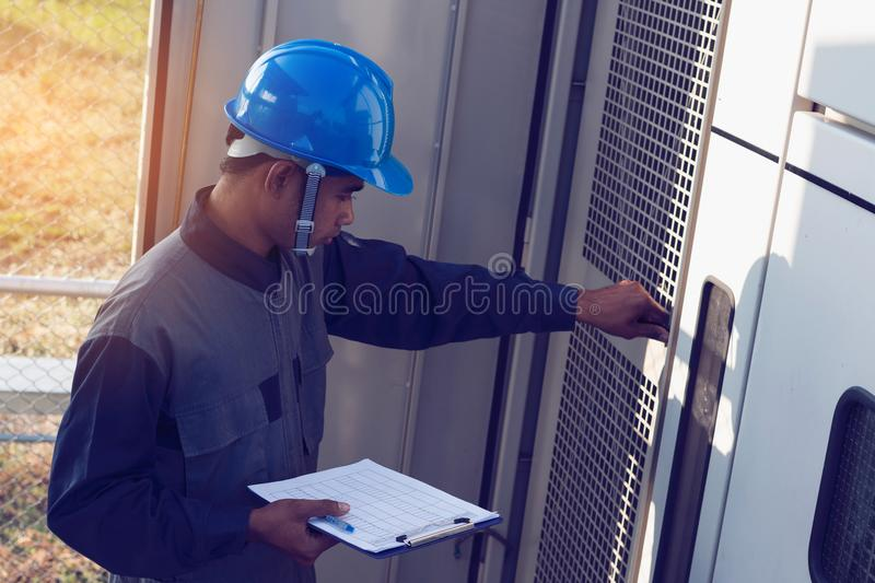 engineer or electrician working on checking and maintenance equipment at green energy solar power plant; checking status step up stock image