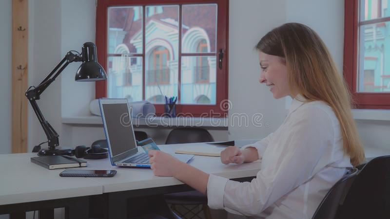 Engineer entering data on pc. Young caucasian architect working in creative office. Professional designer sitting the the table with blueprint. Lady wearing in royalty free stock photography
