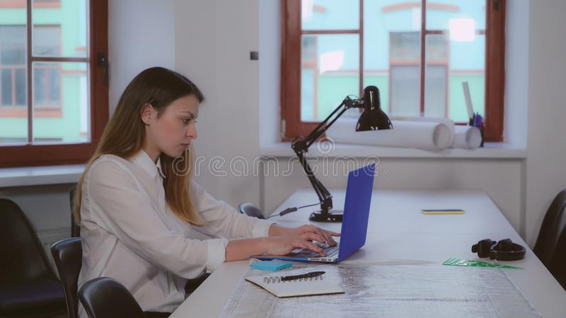 Engineer entering data on pc. Young caucasian architect working in creative office. Professional designer sitting the the table with blueprint. Lady wearing in royalty free stock images