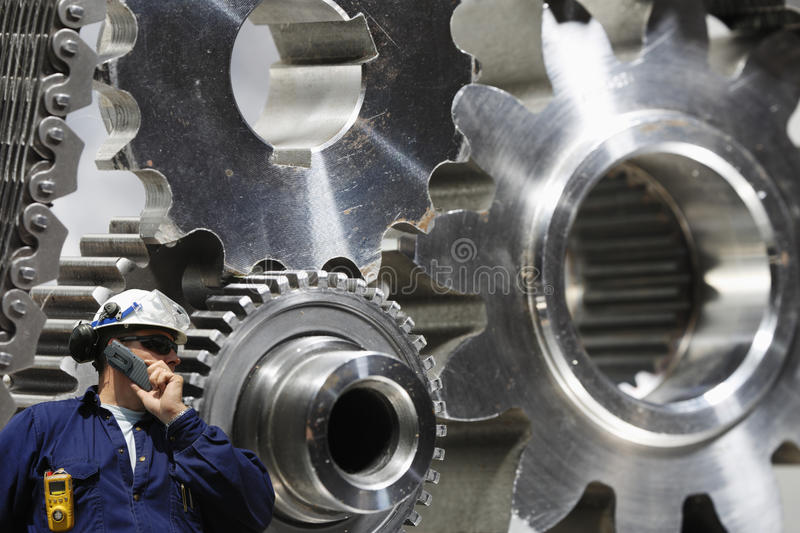 Engineer examining large gears and cog machinery. Engineer, worker talking in phone with large industrial titanium and steel gears in background royalty free stock image