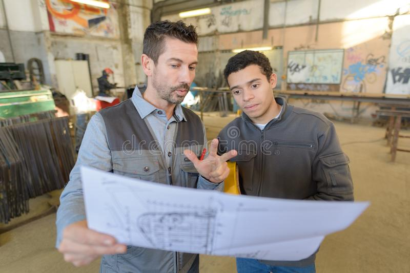 Engineer explaining blueprint to factory staff royalty free stock image