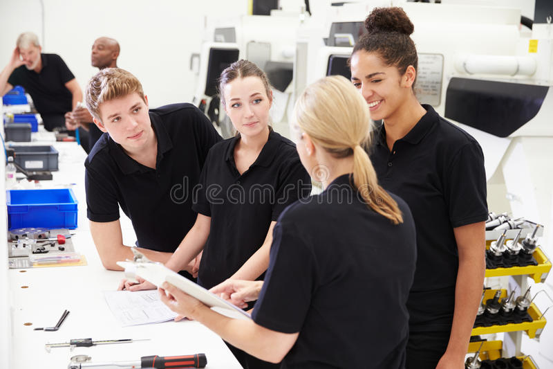 Engineer In Factory With Apprentices Checking Components royalty free stock photography