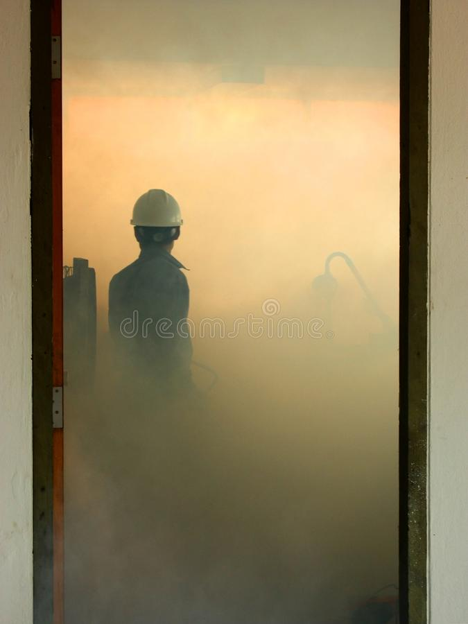 Engineer fighting fire by fire extinguisher in control room with royalty free stock photo