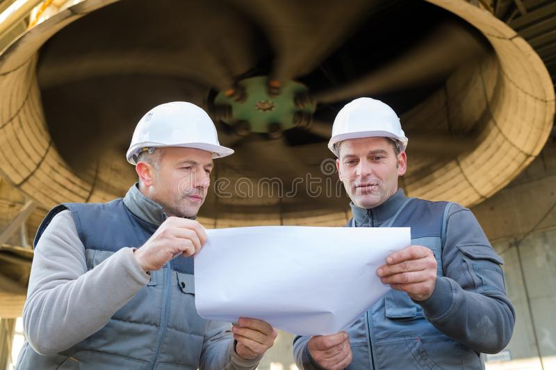 Engineer and foreman pointing to drawing paper royalty free stock images
