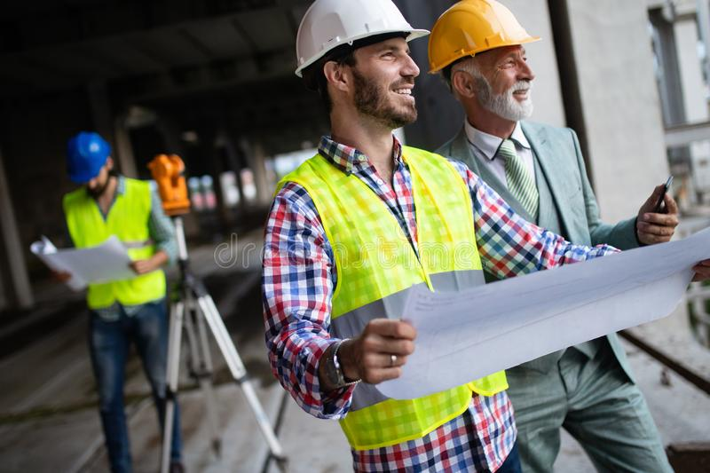Engineer, foreman and worker discussing in building construction site royalty free stock photo